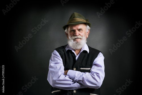 Foto Old bavarian man in hat on black background
