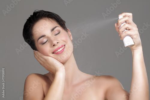 Photo  Beautiful woman applying spray water on face