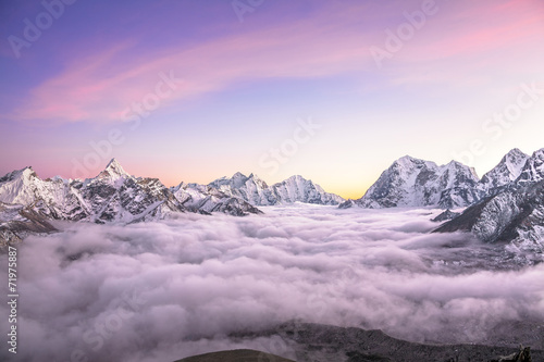Foto op Plexiglas Purper Mountain valley filled with curly clouds at sunrise. Himalayas.