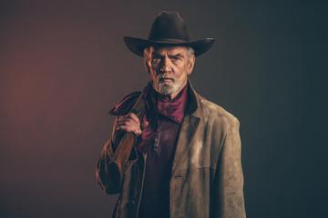 Stary szorstki zachodni kowboj z szarą brodą i brązowym kapeluszem trzyma r
