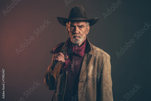 Fotografia, Obraz Old rough western cowboy with gray beard and brown hat holding r