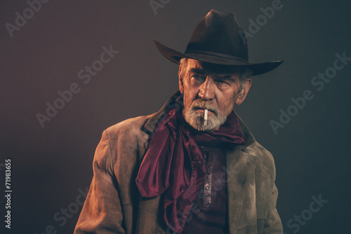 Fototapeta Old rough western cowboy with gray beard and brown hat smoking a