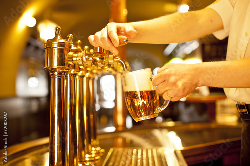 gold beer in the hand and beer taps Принти на полотні