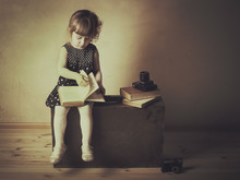 Little Girl Reading A Book On The Old Suitcase