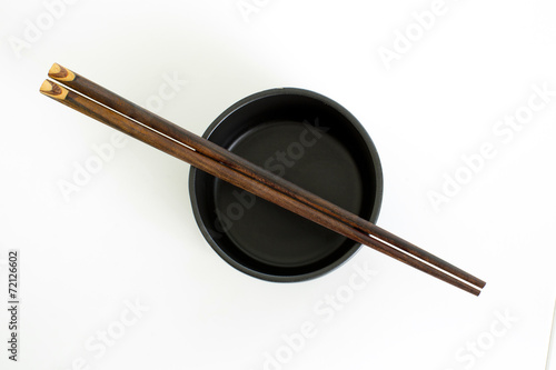 traditional empty rice bowl with bamboo chopsticks on old wood p