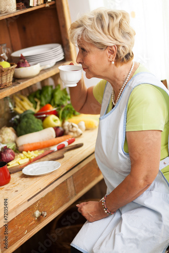 Senior woman  drinking coffee in her kitchen