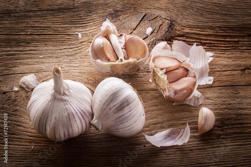 Fotografie, Obraz  Garlic bulbs and cloves on wooden table, closeup