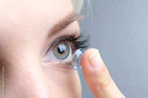 Fotografía  Medicine and vision concept - young woman with contact lens,