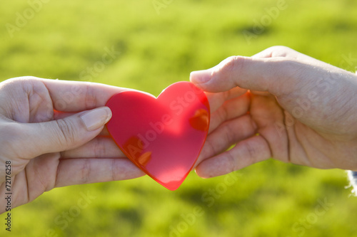 Fotografia  Hand to pass the thing of red heart-shaped