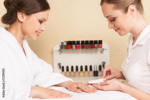 Photo  Close-up Of Beautician Hand Filing Nails Of Woman In Salon.