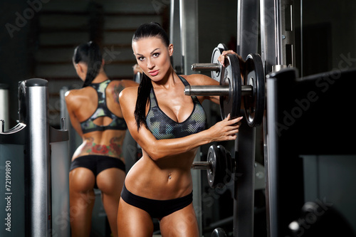 Fotografie, Obraz  athletic young sexy girl sets weight on barbell in the gym