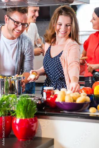 Obraz na plátně  Freunde kochen Pasta und Fleisch zuhause in Küche