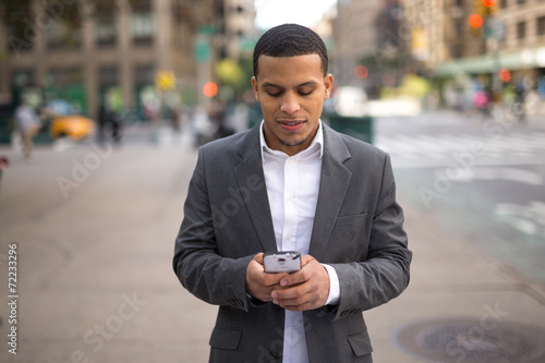 Fotografie, Obraz  Young African American black Latino man texting cellphone