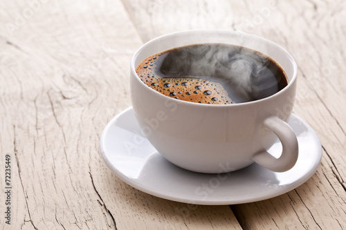 Cup of hot coffee on an old wooden table.