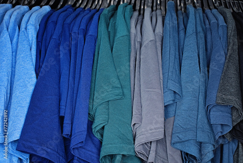 Photo sur Aluminium Aquarelle avec des feuilles tropicales Ein große Anzahl verschieden farbige T-Shirts hängen auf Bügeln