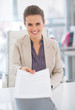 Portrait of happy business woman giving document
