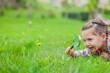 Leinwandbild Motiv little cute girl with magnifying glass examining flower