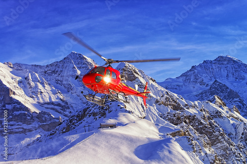 Türaufkleber Hubschrauber Red helicopter landing at swiss ski resort near Jungfrau mountai