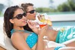 Young couple with drinks by swimming pool