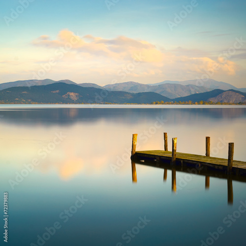 Poster Lac / Etang Wooden pier or jetty and on a blue lake sunset and sky reflectio