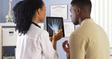 Black Female Doctor Sharing Hand X Ray With Patient On Tablet