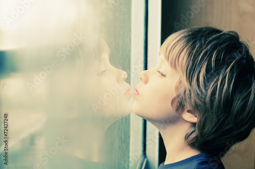 Photo Cute 6 years old boy looking through the window
