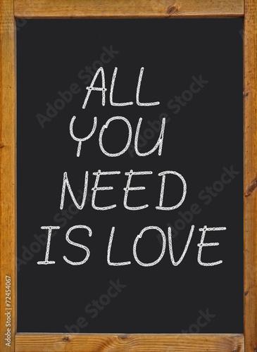 Photo  All you need is love written on a blackboard