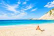 Young woman sitting on beautiful Petani beach, Kefalonia island