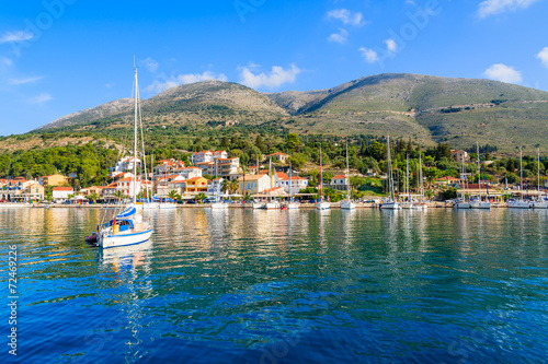 Yacht on sea and view of Agia Efimia fishing village, Kefalonia Wallpaper Mural