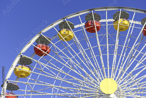 Staande foto Amusementspark Colorful Ferris Wheel in amusement park with blue sky