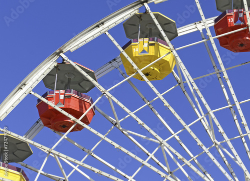 Poster Amusementspark Colorful Ferris Wheel in amusement park with blue sky