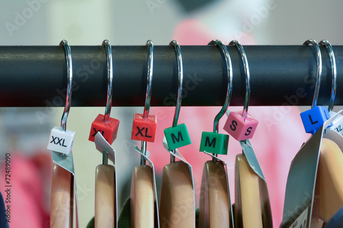 Hangers with clothes and sizes on rail Fototapet