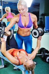 FototapetaBeautiful women exercising with personal fitness trainer