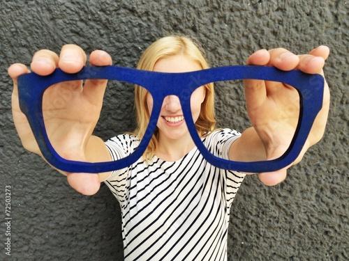 Fotografía  Mädchen hält Brille vor Augen