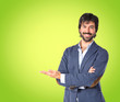 Leinwandbild Motiv Businessman presenting something over green background