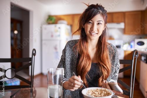 Fotografía  asian teen girl in kitchen eating breakfast with smartphone