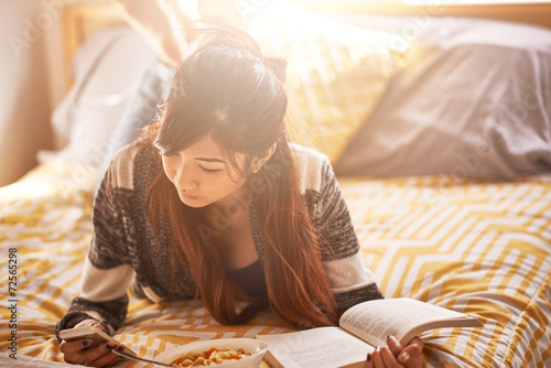 Fotografie, Obraz  asian teen on bed with smartphone, book, and soup