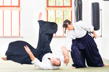 Fototapeta Sztuki walki Man and woman fighting at Aikido martial arts school
