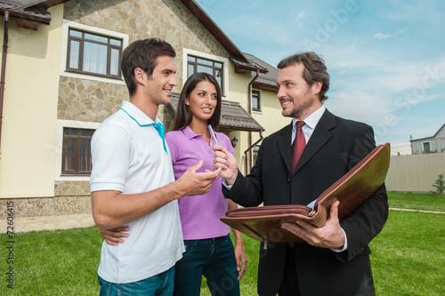 Fotografía  Joven pareja firma el alquiler de contrato con el agente de bienes raíces
