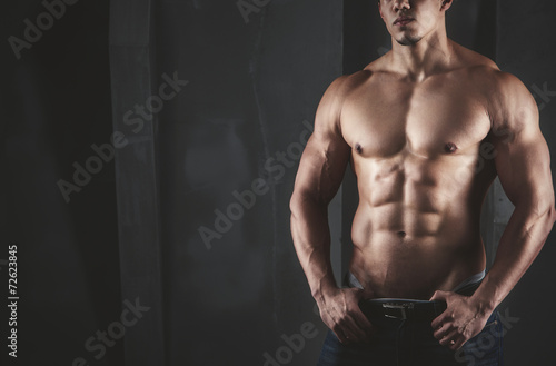 Fotografie, Tablou  Close up of young muscular man lifting weights