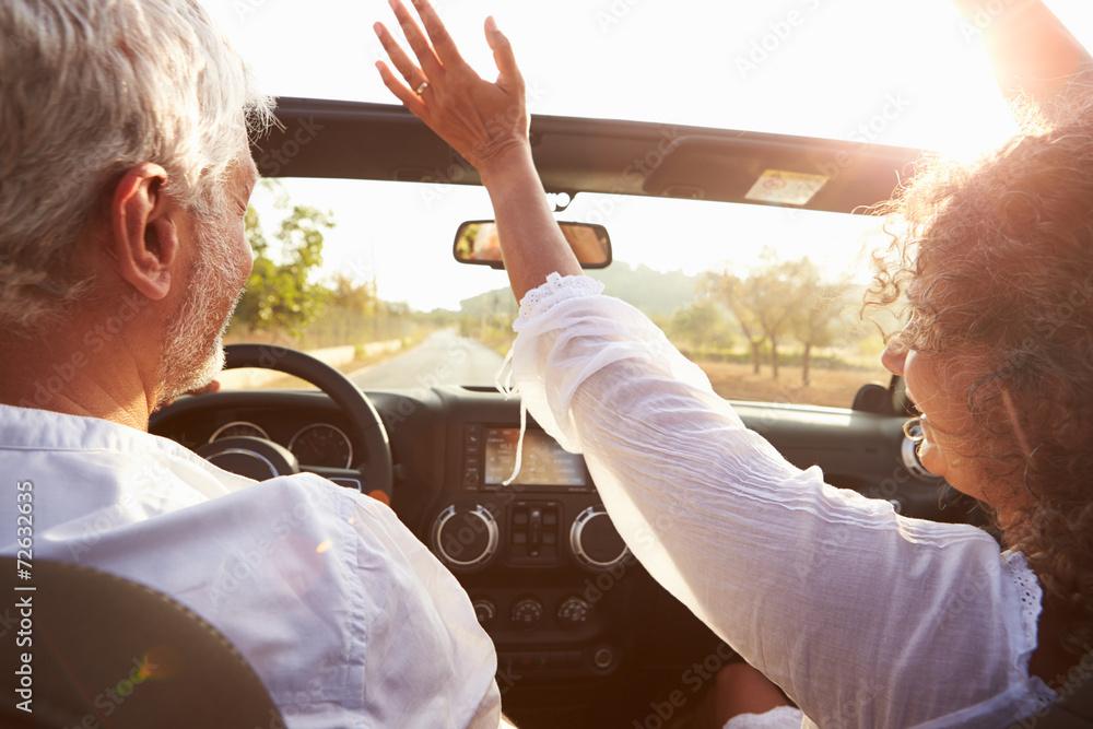 Leinwandbild Motiv - Monkey Business : Mature Couple Driving Along Country Road In Open Top Car