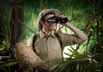 Fototapeta Explorer in the jungle with binoculars