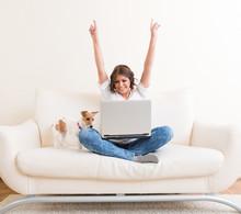 Joyful Woman Using Laptop On The Sofa