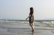 Young woman walking on tropical sea coast