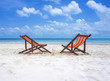 Two beach chairs on the white sand beach before blue sea