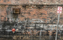 Cluttered Old Brick Wall Background With Graffiti