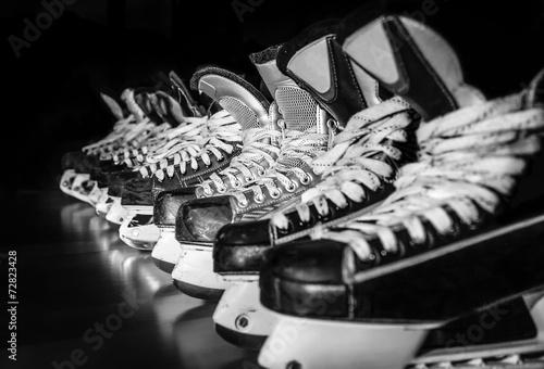 Hockey skates lined up in locker room Poster