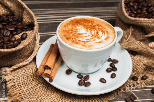 Fototapeta Cappuccino in a white cup with cinnamon and drawing on milk obraz