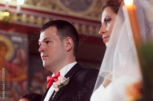 Fotografie, Obraz  bride and groom in church front of priest