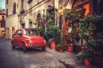 Stary zabytkowy kultowy samochód zaparkowany na ulicy przy restauracji